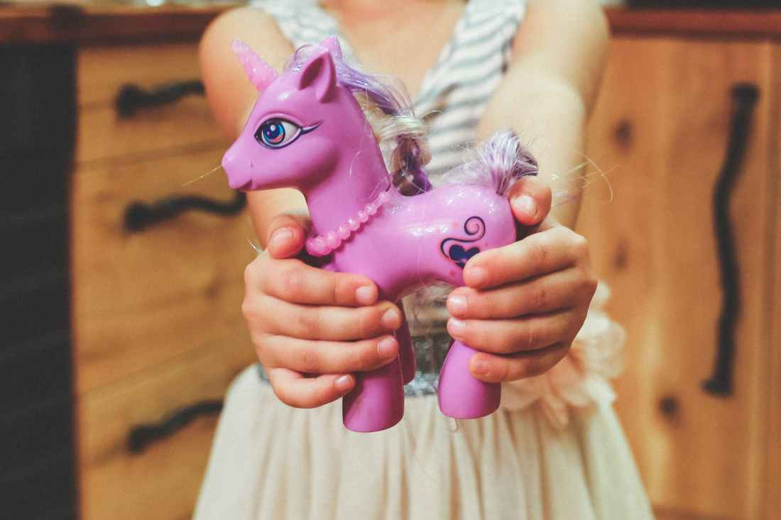 child holding unicorn toy